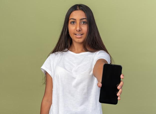 Młoda dziewczyna w białej koszulce pokazująca smartfona patrząca na kamerę uśmiechnięta pewnie stojąca nad zielenią