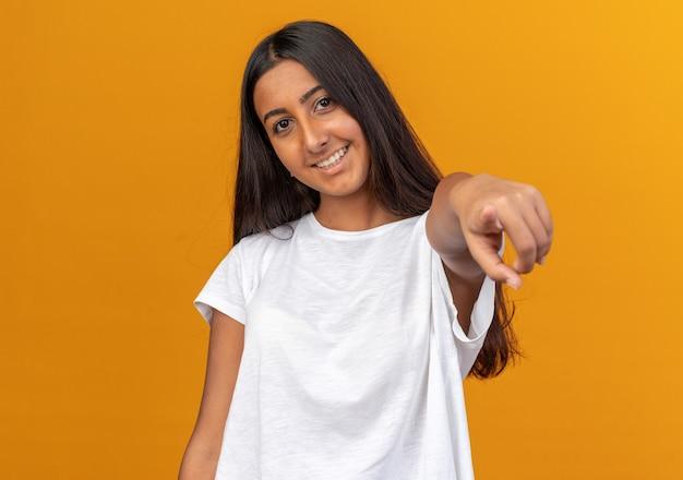 Młoda dziewczyna w białej koszulce szczęśliwa i pozytywnie wskazująca palcem wskazującym na aparat uśmiechający się radośnie stojąc na pomarańczowym tle