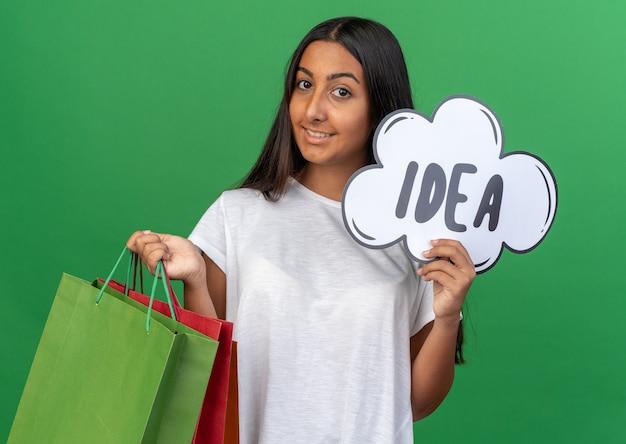Młoda dziewczyna w białej koszulce trzyma papierowe torby i znak dymek z pomysłem na słowo patrząc na kamery uśmiechając się radośnie stojąc na zielonym tle