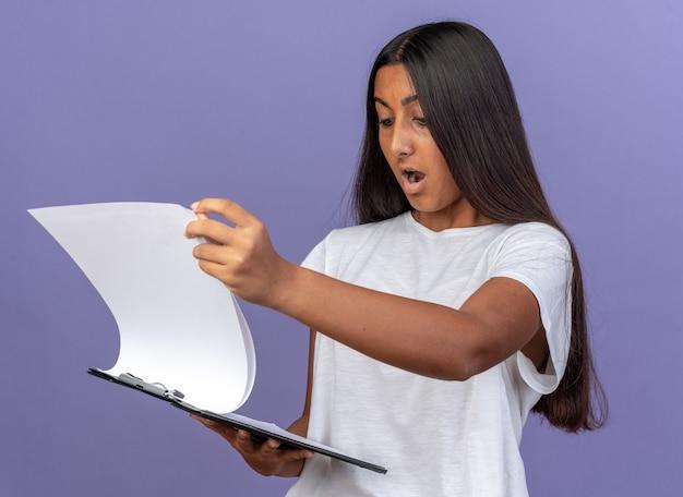 Młoda dziewczyna w białej koszulce trzyma schowek z pustymi stronami, patrząc na to zdumiona i zdziwiona, stojąc na niebiesko