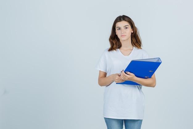 Młoda dziewczyna w białej koszulce trzymając folder i patrząc rozsądnie, widok z przodu.