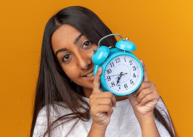 Młoda dziewczyna w białej koszulce trzymająca budzik, patrząca na kamerę ze szczęśliwą twarzą i uśmiechem