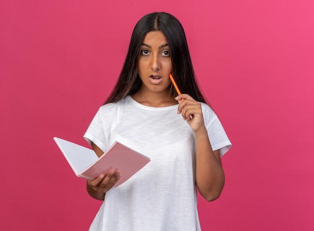 Młoda dziewczyna w białej koszulce trzymająca notatnik i ołówek patrząca na kamerę zdziwiona