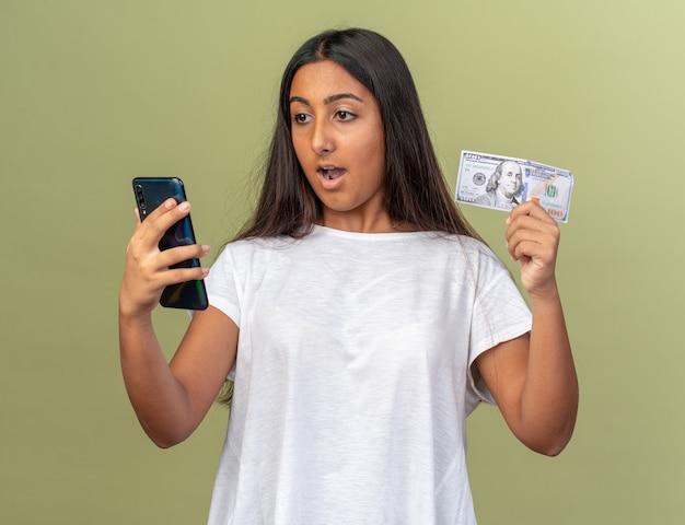 Młoda dziewczyna w białej koszulce trzymająca smartfona i gotówkę, patrząca na ekran swojego telefonu komórkowego, zaskoczona i szczęśliwa