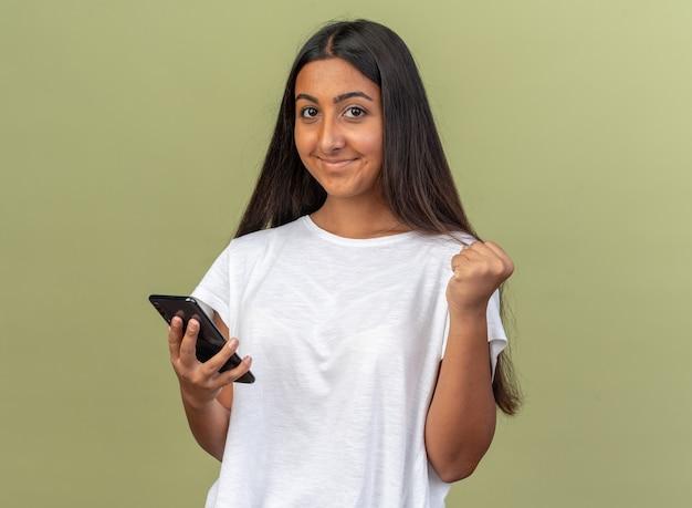 Młoda dziewczyna w białej koszulce trzymająca smartfona patrząca na kamerę szczęśliwa i podekscytowana zaciskająca pięść