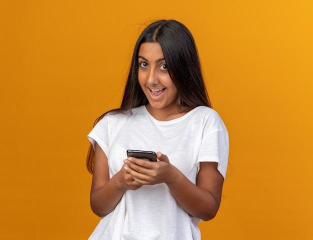 Młoda dziewczyna w białej koszulce trzymająca smartfona patrząca na kamerę z szczęśliwą twarzą uśmiechającą się radośnie