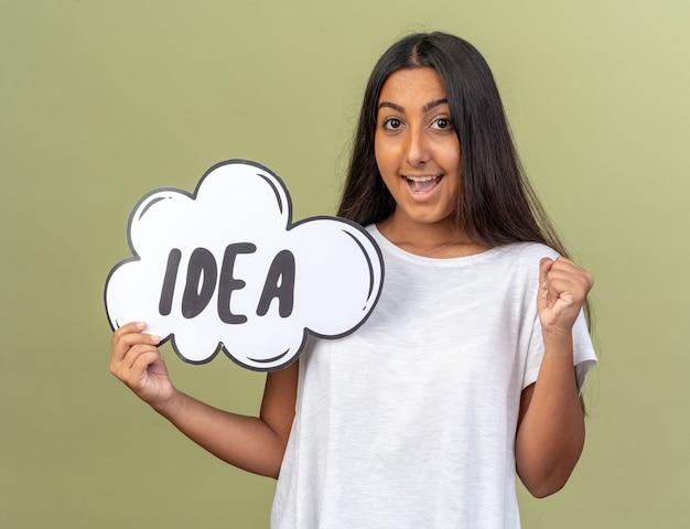 Młoda dziewczyna w białej koszulce trzymająca znak dymka zaciskająca pięść uśmiechnięta radośnie z pomysłem na słowo stojącym nad zielonym tłem