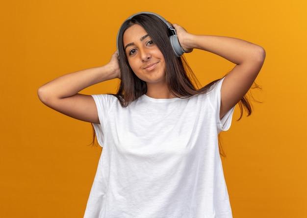Młoda dziewczyna w białej koszulce ze słuchawkami szczęśliwa i pozytywnie patrząca na aparat uśmiechający się, cieszący się ulubioną muzyką stojącą na pomarańczowym tle