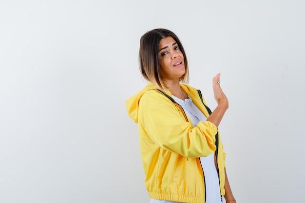 Młoda dziewczyna w białej koszulce, żółtej kurtce, podnosząc rękę, machając, witając kogoś i wyglądając sympatycznie, widok z przodu.