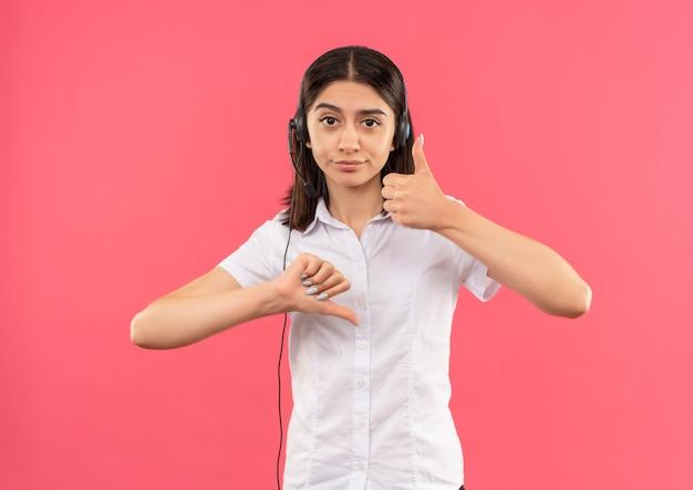 Młoda dziewczyna w białej koszuli i słuchawkach, patrząc w przód pokazując kciuki w górę iw dół stojąc na różowej ścianie