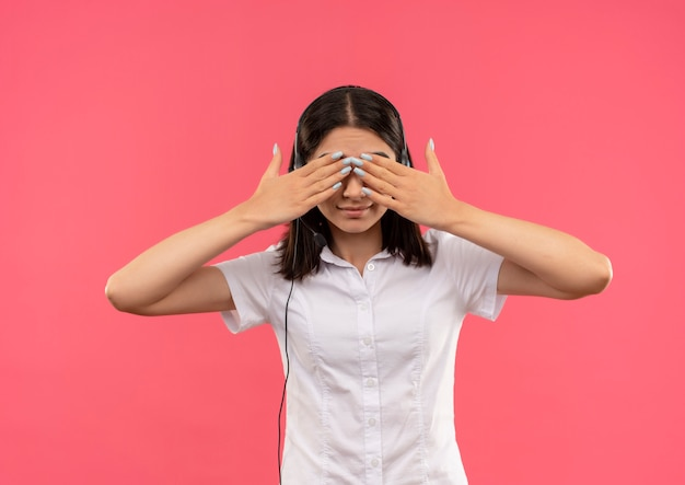 Młoda dziewczyna w białej koszuli i słuchawkach, zasłaniając oczy rękami stojącymi na różowej ścianie