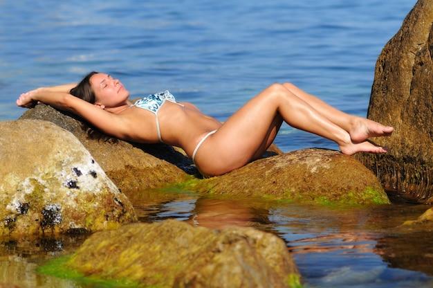 Młoda dziewczyna w biało-niebieskim stroju kąpielowym z zamkniętymi oczami, siedząc na dużym głazie w pobliżu morza