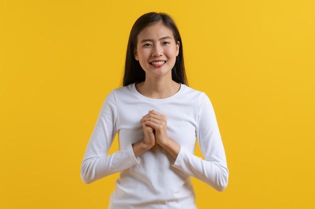 Młoda dziewczyna w białym dorywczo wygląda uśmiech i czuje się wdzięczna.