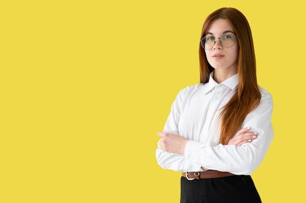 Młoda dziewczyna w białym rublu na białym tle na żółtej ścianie