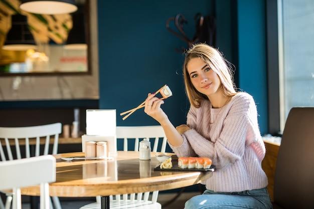 Młoda dziewczyna w białym swetrze je sushi na obiad przy małej kawiarni