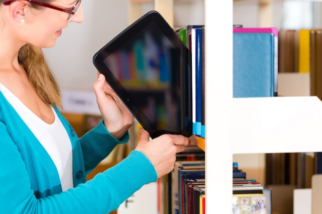 Młoda dziewczyna w bibliotece z ebook lub pastylki komputerem