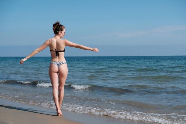 Młoda dziewczyna w bikini cieszy się morze