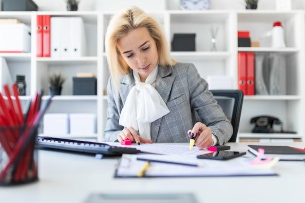 Młoda dziewczyna w biurze pracuje z markierem i dokumentami.