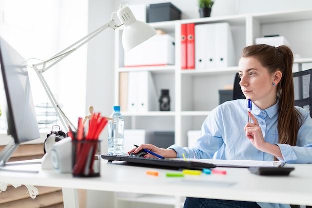 Młoda dziewczyna w biurze siedzi przy stole, trzyma w ręce długopis i pracuje przy komputerze.
