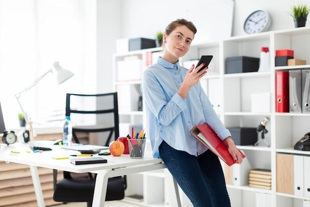 Młoda dziewczyna w biurze stoi, opiera się na stole i trzyma telefon oraz teczkę z dokumentami.