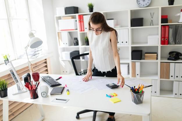 Młoda dziewczyna w biurze stoi przy stole i patrzy na dokumenty.