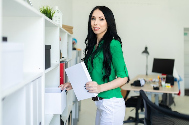 Młoda dziewczyna w biurze wyjmuje białe pudełko.
