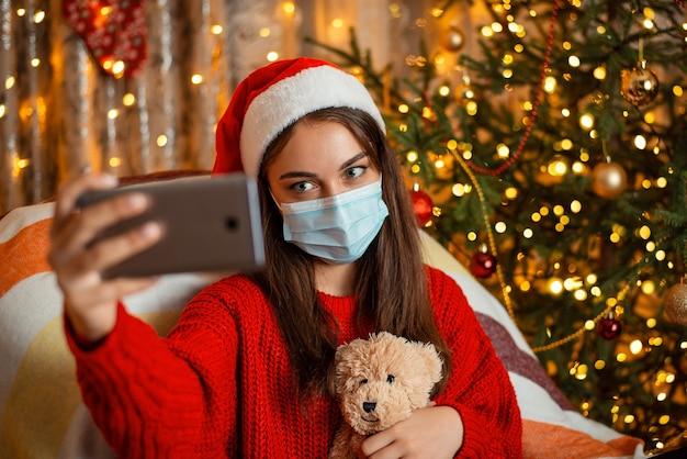 Młoda dziewczyna w boże narodzenie kapelusz siedzi w fotelu i biorąc selfie przez smartfona