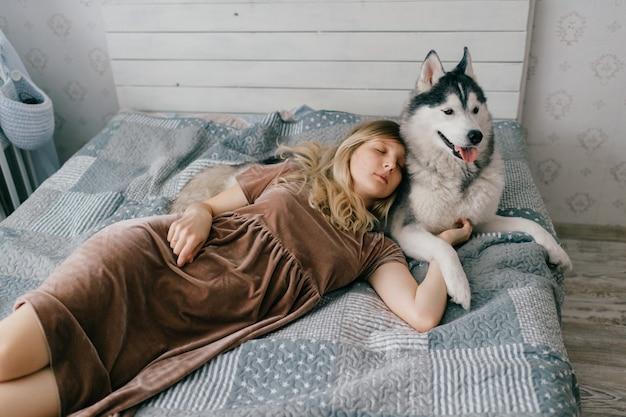 Młoda dziewczyna w brązowej sukni, leżąc na łóżku w domu i spanie z husky szczeniaka.