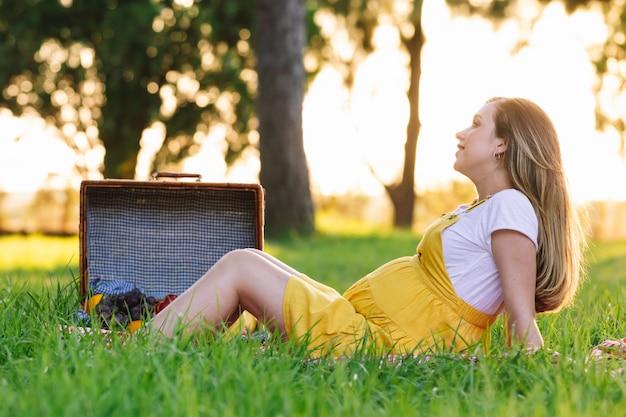 Młoda dziewczyna w ciąży na pikniku o zachodzie słońca. czuć się dobrze