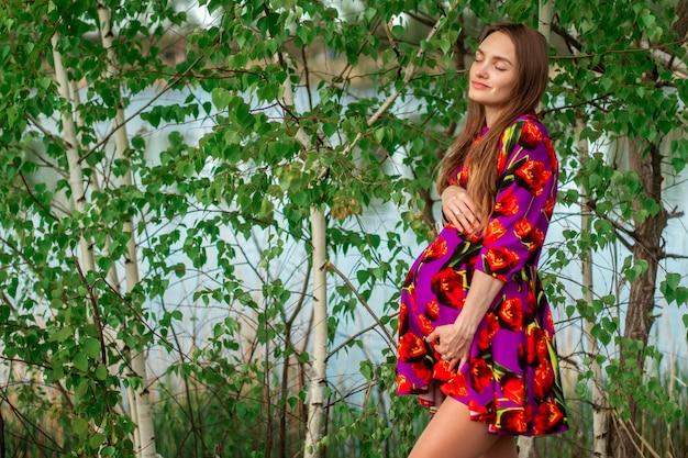 Młoda dziewczyna w ciąży w sukni w naturze
