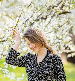 Młoda dziewczyna w ciemnej sukni zostaje blisko kwitnącego drzewa