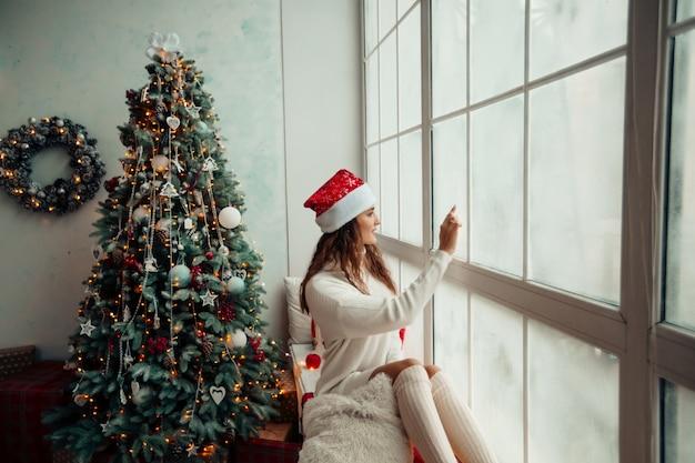 Młoda dziewczyna w czapce świętego mikołaja siedzi na parapecie i rysuje na zaśnieżonym oknie