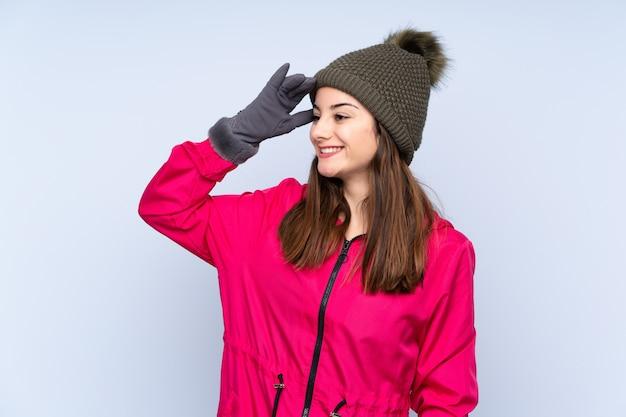Młoda dziewczyna w czapce zimowej na niebieskiej ścianie coś sobie uświadomiła i zamierza rozwiązać problem
