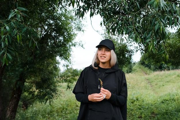 Młoda dziewczyna w czarnej czapce i bluzie z kapturem na zewnątrz. portret uśmiechniętej dziewczyny