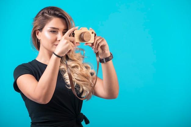 Młoda dziewczyna w czarnej koszuli powiesiła na szyi zabawkowy aparat i zrobiła zdjęcie.