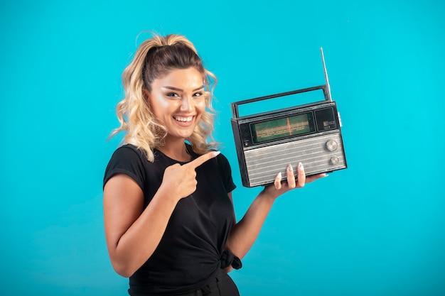 Młoda dziewczyna w czarnej koszuli trzyma vintage radio i czuje się pozytywnie.