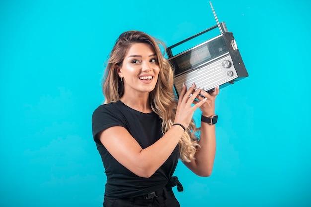 Młoda dziewczyna w czarnej koszuli, trzymając vintage radio i słuchając go.