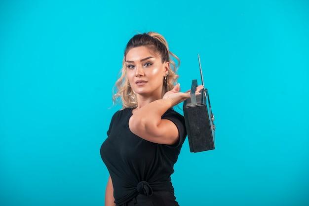 Młoda dziewczyna w czarnej koszuli, trzymając vintage radio na plecach.