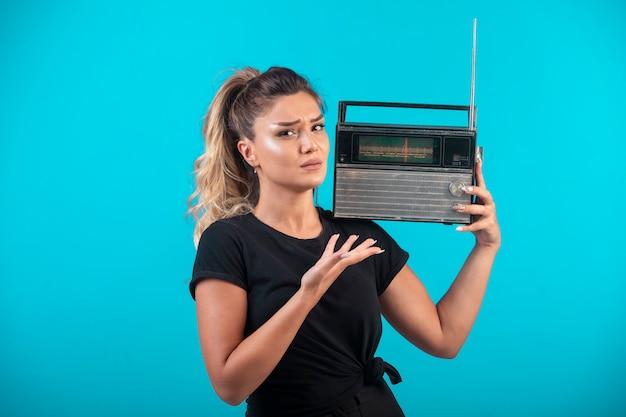 Młoda dziewczyna w czarnej koszuli, trzymając vintage radio na ramieniu.