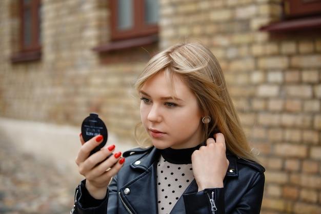 Młoda dziewczyna w czarnej kurtce, sprawdzająca, jak wygląda w małym przenośnym lusterku