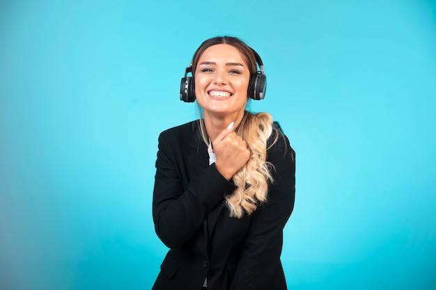 Młoda dziewczyna w czarnej marynarce na sobie słuchawki i dobrą zabawę.