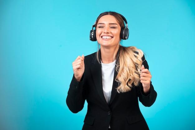 Młoda dziewczyna w czarnej marynarce na sobie słuchawki.
