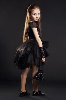 Młoda dziewczyna w czarnej sukni z czarną torbą na czarnym tle. dziewczyna przygotowuje się na święto halloween