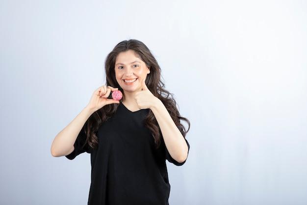 Młoda dziewczyna w czarnym stroju trzyma różowy plik cookie i pokazuje kciuk do góry.