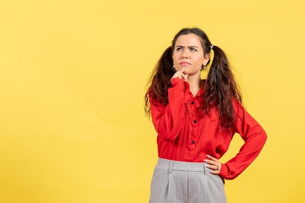 Młoda dziewczyna w czerwonej bluzce pozowanie i myśli na żółto