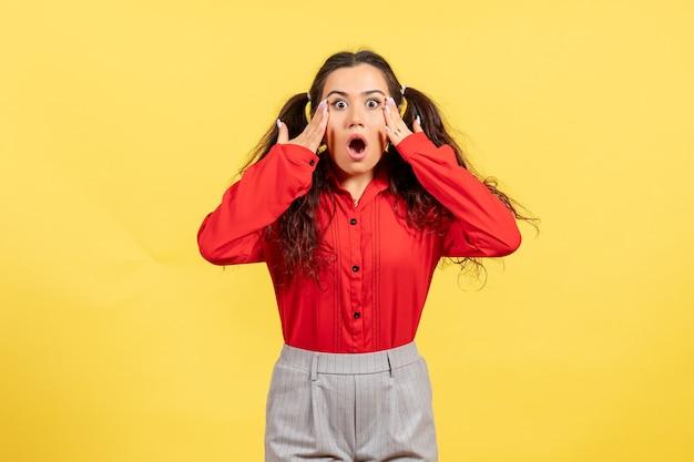 Młoda dziewczyna w czerwonej bluzce pozowanie z wstrząśniętą twarzą na żółto