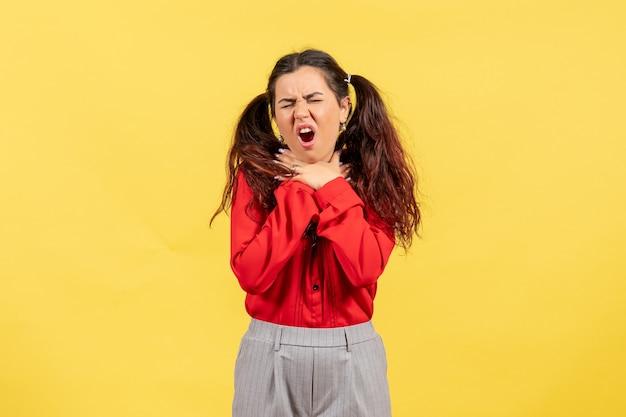 Młoda dziewczyna w czerwonej bluzce z bólem gardła na żółto
