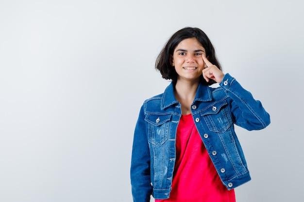 Młoda dziewczyna w czerwonej koszulce i dżinsowej kurtce kładzie palec wskazujący na twarzy i wygląda na szczęśliwą