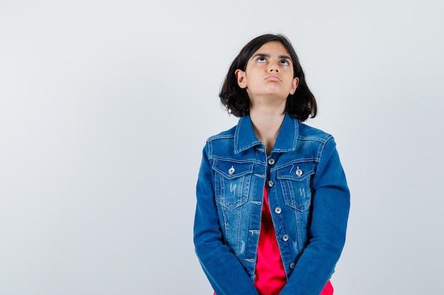 Młoda dziewczyna w czerwonej koszulce i dżinsowej kurtce, myśląc o czymś i patrząc zamyślony, widok z przodu.
