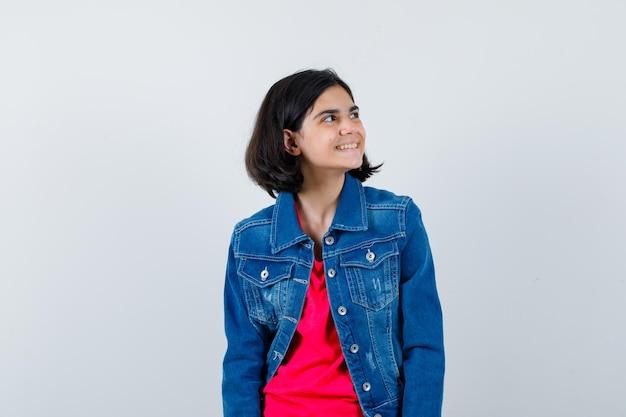 Młoda dziewczyna w czerwonej koszulce i dżinsowej kurtce, odwracając wzrok, pozując do kamery i wyglądając na szczęśliwą